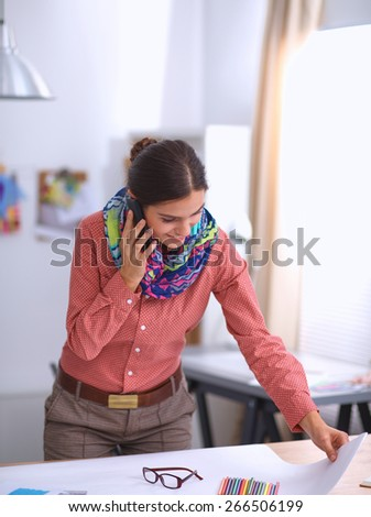 Young attractive female fashion designer working at office desk, drawing while talking on mobile - stock photo