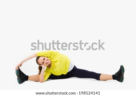 Young attractive female fitness model performing a twine, looking at the camera and smiling - stock photo