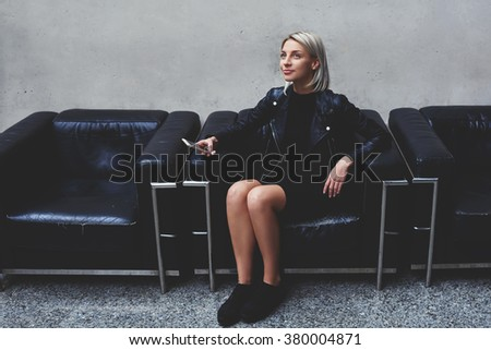 Young attractive female looking up and thinking about what to write in text messaging on mobile phone, stylish hipster girl dreaming after cell telephone conversation while sitting in modern studio - stock photo
