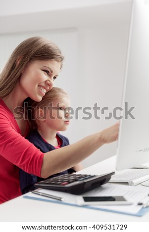 Young attractive female pointing at computer screen showing smth to her small daughter. Young family browsing internet and doing on-line purchases.  - stock photo