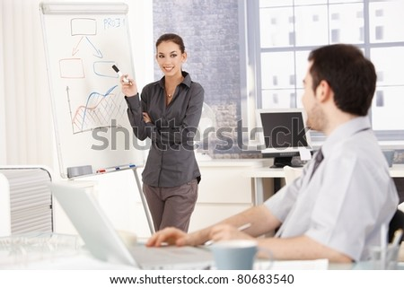 Young attractive female presenting in office over whiteboard, smiling. - stock photo