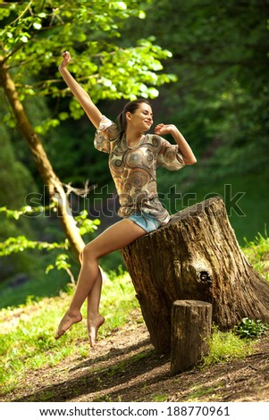 Young attractive female relaxing in nature on beautiful summer day.
