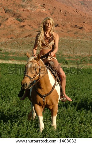 young attractive female rides horseback in red canyon region of southern utah - stock photo