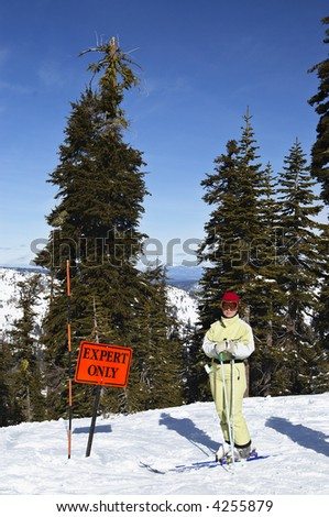 "Young attractive female skier poses next to ""Experts only"" sign at skiing resort at Lake Tahoe. - stock photo"
