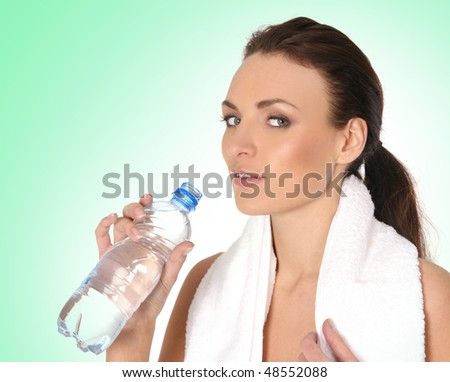 Young attractive female sportsman drinking water over blue background