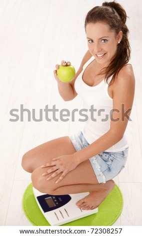 Young attractive female squatting on scale, holding an apple in hand, smiling, dieting.? - stock photo