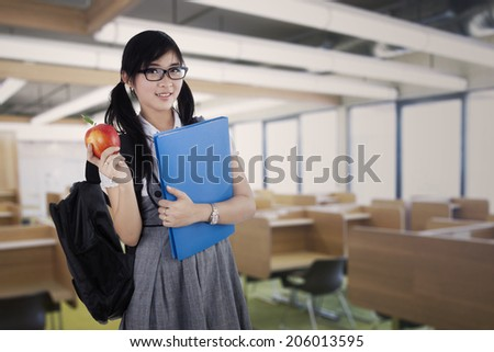 Young attractive female student standing in the classroom while holding a red apple and folder