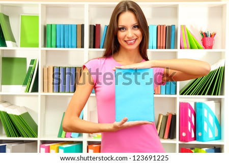 Young attractive female student with book in library