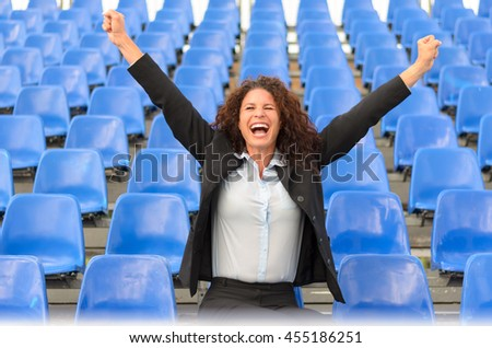 Young attractive female supporter cheering her team as she stands alone in empty blue seating in a stadium or auditorium - stock photo