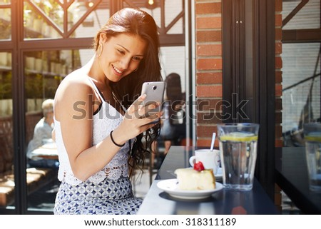 Young attractive female taking picture of her coffee shop breakfast with mobile phone camera, smiling gorgeous latin woman photographing cake with berries on her cell phone, people using technology - stock photo