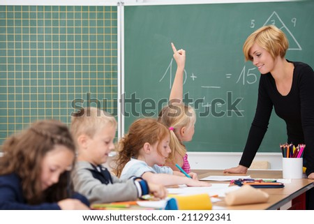 Young attractive female teacher interacting with her young primary school students asking a young girl for an answer - stock photo