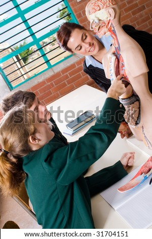Young attractive female teacher teaching human anatomy at biology class - stock photo