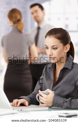Young attractive female using laptop in office, colleagues chatting in background.