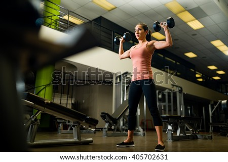 Young attractive female working out in a gym with dumbbells