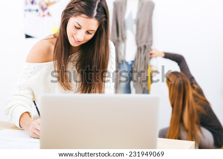 Young attractive females fashion designers leaning on office desk, working with a laptop - stock photo