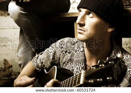 Young attractive fit man playing guitar with passion