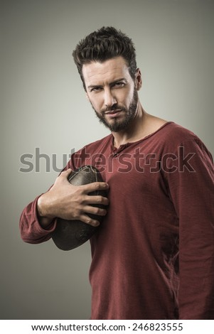 Young attractive football player playing with ball on gray background - stock photo