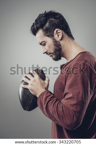 Young attractive football player with ball on gray background - stock photo