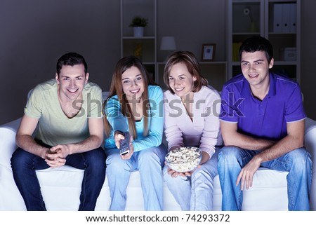 Young attractive friends watch TV at home - stock photo