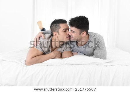 young attractive gay men couple lying on bed together in bedroom kissing and cuddling happy in love wearing casual clothes in homosexual relationship concept - stock photo
