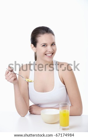 Young attractive girl breakfast corn flakes on a white background - stock photo
