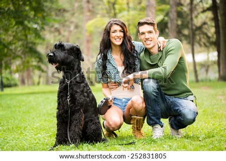 Young attractive girl crouches in the park with her boyfriend next to the dog, a black giant schnauzer. With a smile looking at the camera.