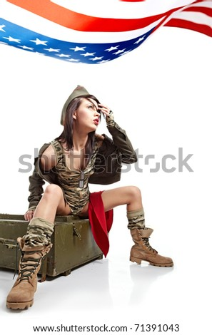 Young attractive girl dressed in old battle coat sitting . Vintage style studio shot. - stock photo