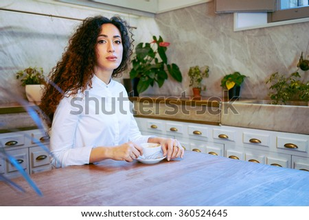 young attractive girl drinking coffee in a coffee-shop.Beautiful business woman drinking coffee before a meeting with a business-partner - stock photo