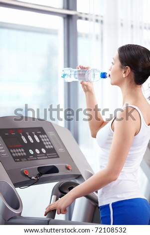 Young attractive girl drinks water in the fitness club
