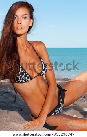 Young attractive girl enjoys hot summer day at the beach. - stock photo