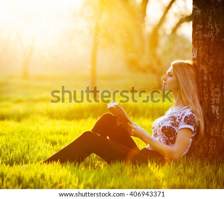 young attractive girl immersed in the world of dreams and fantasy reading a bestseller in the park sitting on the grass in the rays of the setting of the spring sun. dressed in trendy jeans - stock photo