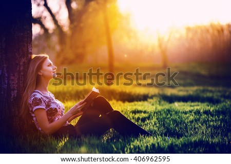 young attractive girl immersed in the world of dreams and fantasy reading a bestseller in the park sitting on the grass in the rays of the setting of the spring sun.to know the truth by reading  book. - stock photo