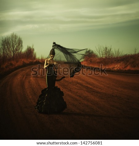 Young attractive girl in a black dress posing outdoors. Grain added - stock photo