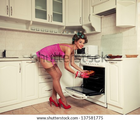 Young attractive girl in beautiful clothes bakes cakes. Pin-up style images. grain added - stock photo