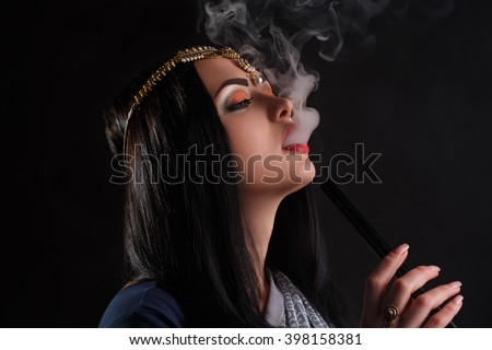 Young attractive girl in blue elegant indian sari smoking narghile hookah. Portrait of indian woman smoking hookah. Black background. Beauty portrait of young indian brunette woman enjoying the hookah - stock photo