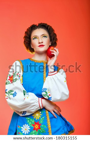Young attractive girl in national costume eastern europe holding apples - stock photo