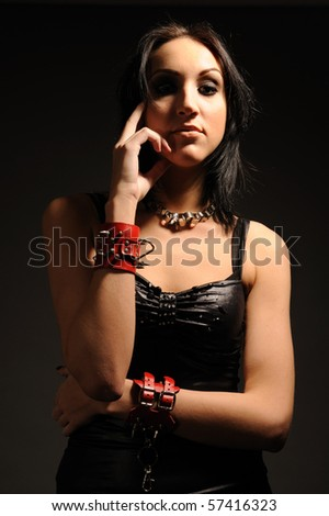 Young attractive girl in red handcuffs, studio shot.