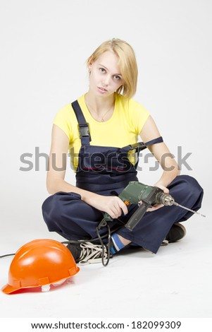 Young attractive girl in the construction overalls with screwdriver in her hands