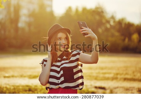 Young attractive girl in the hat makes self on a cellphone. The concept of urban street youth fashion. Communication in social networks. - stock photo
