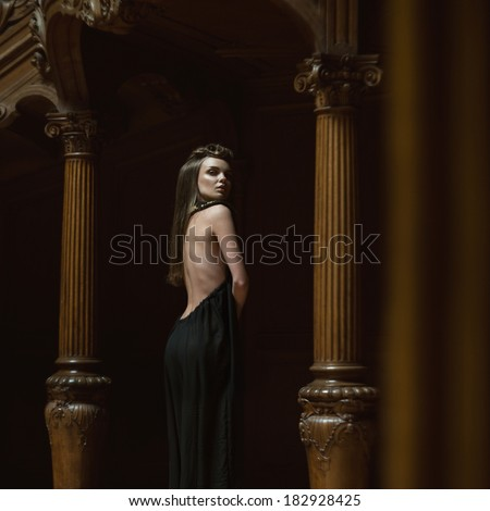 Young attractive girl in the image of princess in rich interior. Grain added - stock photo