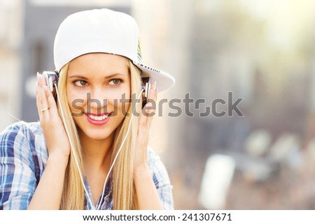 Young attractive girl in urban background listening to music with headphones  - stock photo