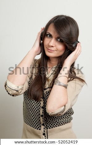 Young attractive girl listening to music looking at camera - stock photo