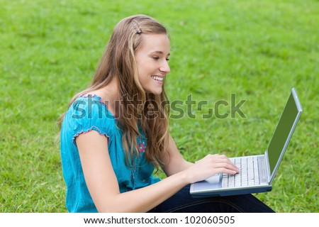 Young attractive girl looking at her laptop while sitting down on the grass in a park