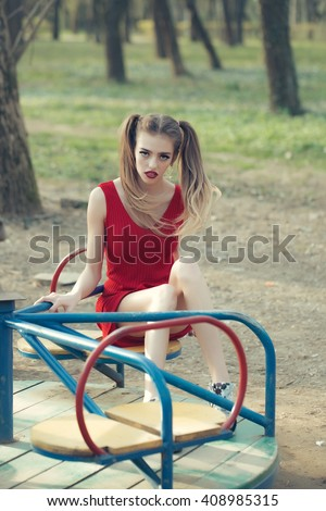 Young attractive girl on carousel in red dress with funny hairstyle outdoor