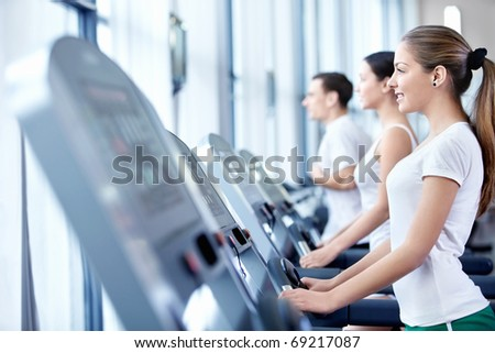 Young attractive girl on the treadmill