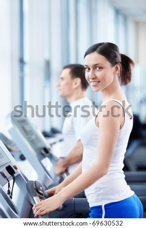 Young attractive girl on the treadmill - stock photo