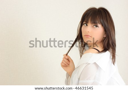 Young attractive girl plays with her hair against the white wall - stock photo