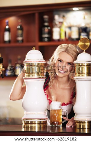Young attractive girl pours a beer at the bar - stock photo