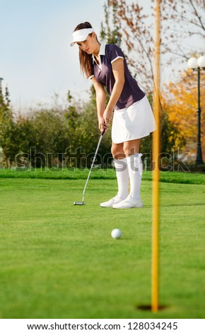 Young attractive girl putting golf ball - stock photo
