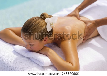Young attractive girl receiving back massage. - stock photo